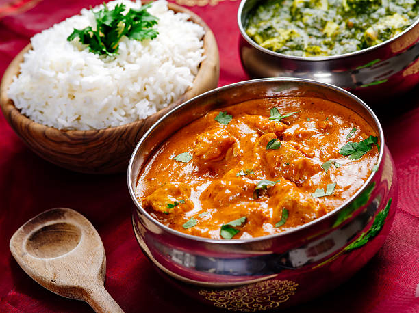 Butter chicken and Saag Paneer Indian dinner Photo of an Indian meal of Butter Chicken, rice and Saag Paneer. Focus across the Butter Chicken bowl. butter chicken stock pictures, royalty-free photos & images
