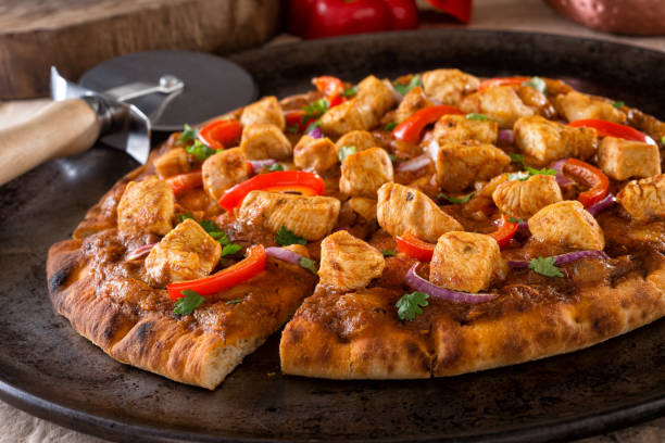 Butter Chicken Pizza A delicious butter chicken pizza with red pepper, red onion and cilantro. naan bread stock pictures, royalty-free photos & images