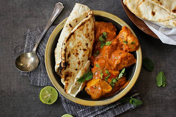 butter chicken served with homemade indian naan bread - cuisine indienne photos et images de collection