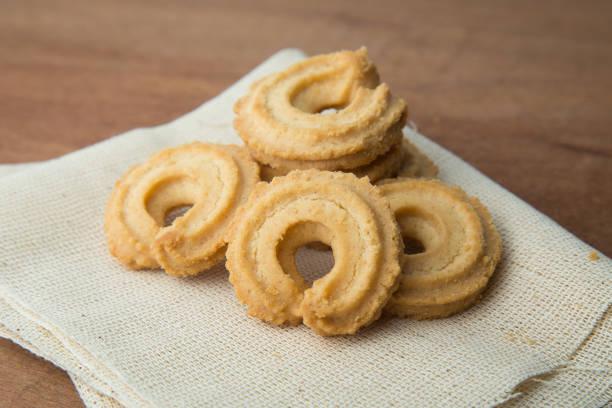butter cookies auf weißem leinen auf holztisch - hausgemachte zuckerplätzchen stock-fotos und bilder