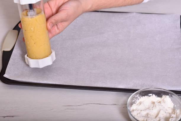 crema de mantequilla para pasteles en una cuchara que llena la pistola de pastelería. Tradiciones de celebración de Navidad y Año Nuevo. - foto de stock