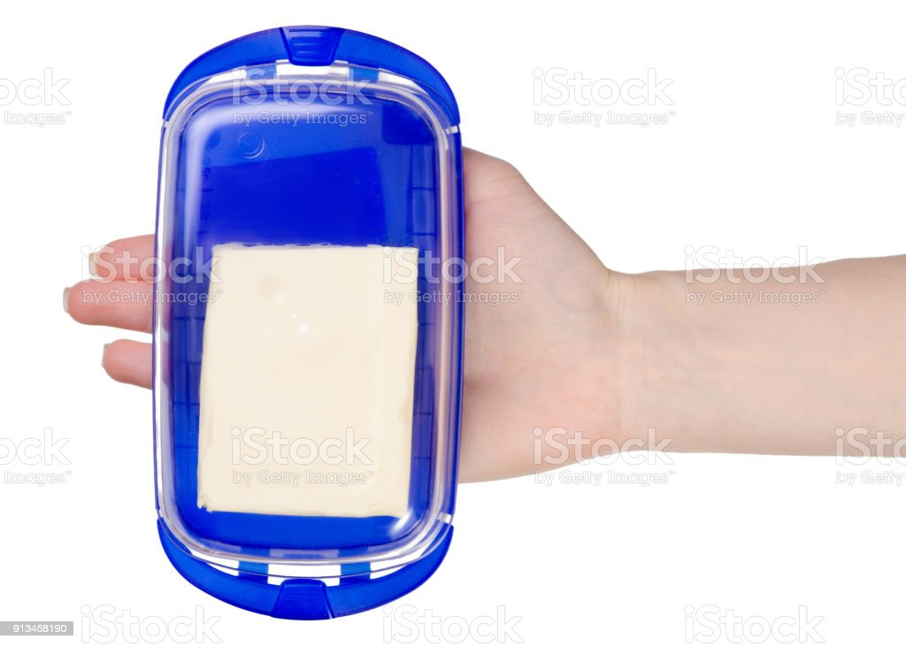 Butter dish in hands stock photo