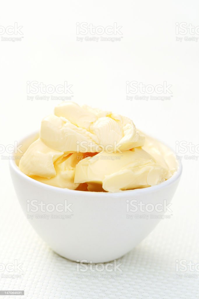 Butter in a white bowl on a white background royalty-free stock photo