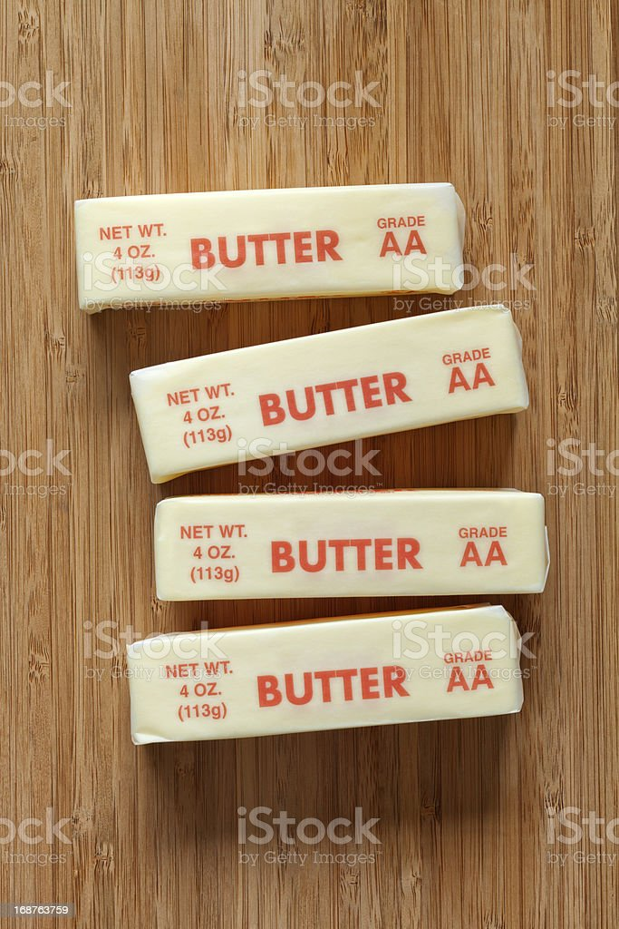 Butter in Wrapper on Cutting Board stock photo