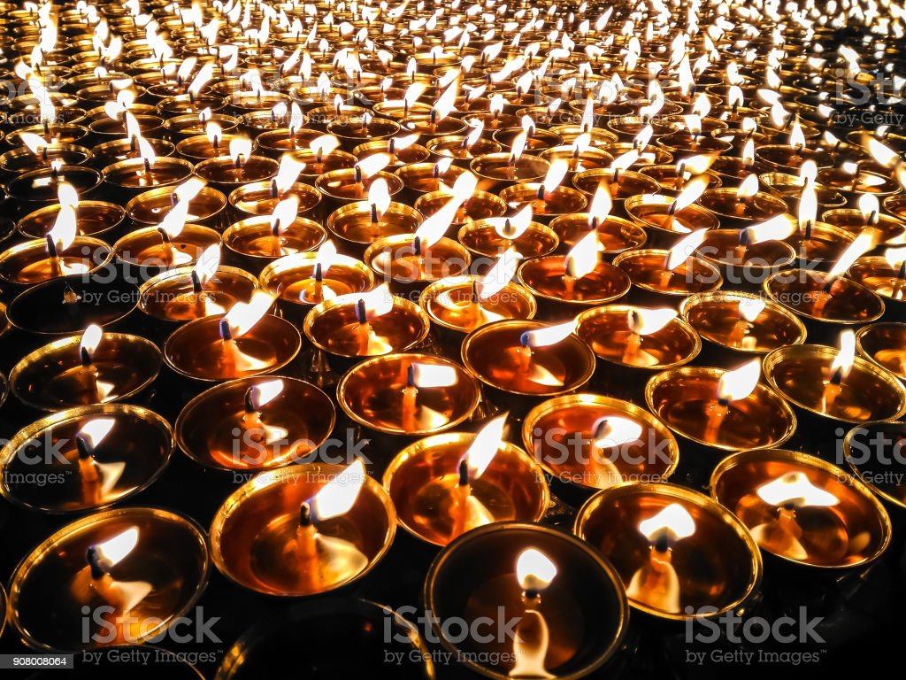 Butter lamps with flames near Bodhnath stupa in Kathmandu valley, Nepal stock photo