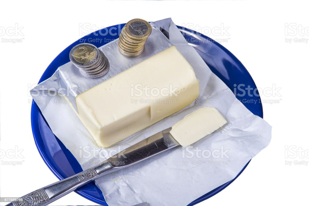 Butter on the blue plate with euro coins money on white. stock photo