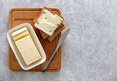 Butter or spread is in white butter-dish standing on a kitchen table and sandwich served on board ready to eat, view from above, space for a text