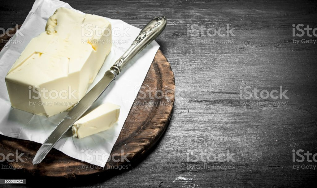 Butter with a knife on the board. stock photo