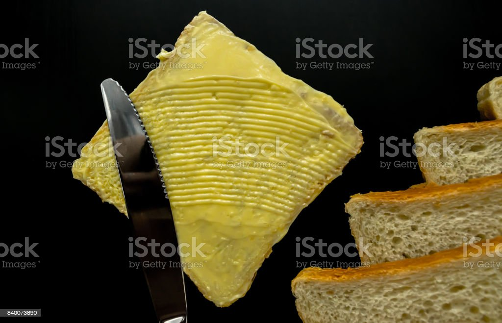 Butter with beautiful stains and a knife on a piece of bread close-up on a dark background stock photo