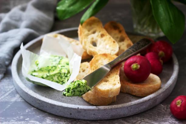 butter mit wildem knoblauch, brotscheiben und radieschen, zutaten für die herstellung eines sandwiches. - bärlauchsalz stock-fotos und bilder