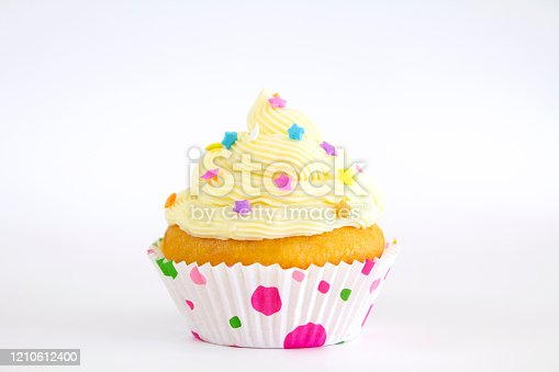 A vanilla buttercream cupcake with sprinkles, isolated on white.