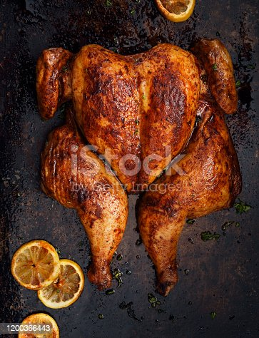 Portuguese butterflied roast chicken in a cooking pan, crapaudine style