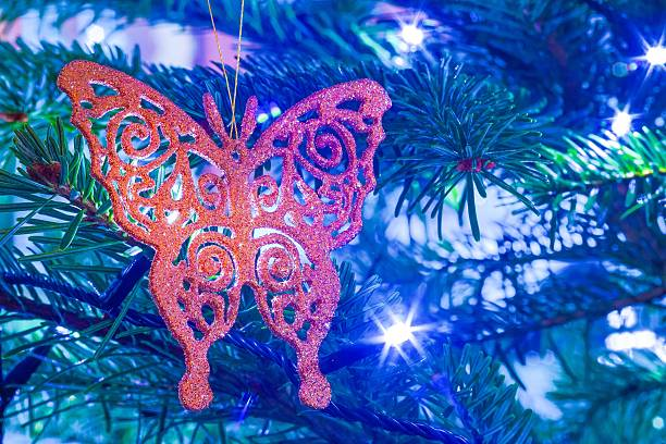 Butterfly gold bouble closeup hanging on real pine Christmas tree stock photo