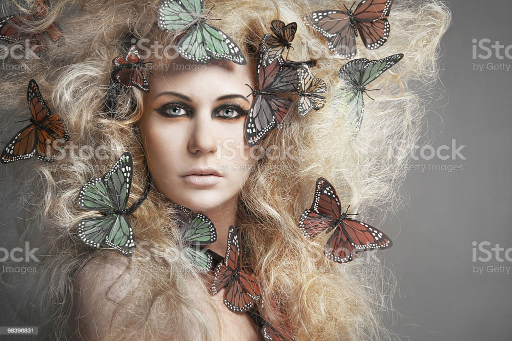 Butterfly in curly blond hair. royalty-free stock photo
