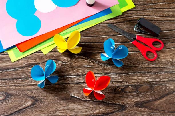 나무 테이블에 나비 종이 장식 또는 여름 화환. 핸드메이드 종이 아이디어. 어린이의 창의력, 공예, 어린이를위한 공예의 프로젝트. 스톡 사진