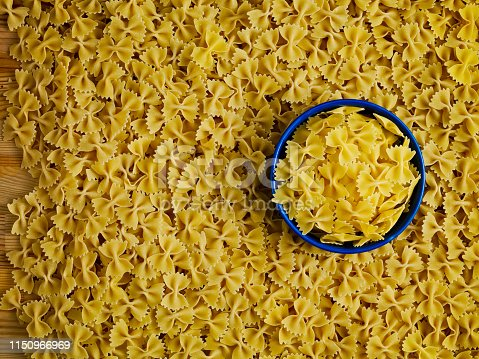 Full frame raw pastas and empty blue bowl