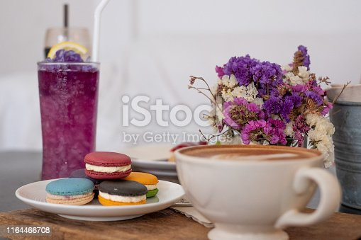 Butterfly pea water and macaron and hot coffee mug in the front