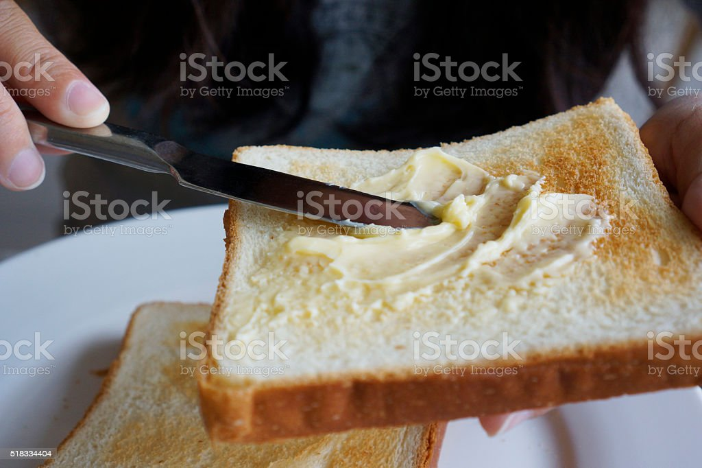 buttering toast with knife stock photo