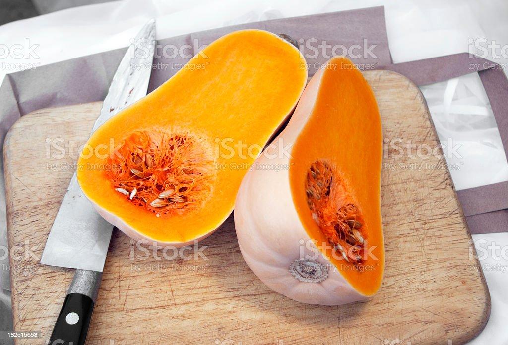 Butternut squash cut in half on wooden cutting board royalty-free stock photo