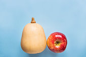 istock Butternut Squash Pumpkin Ripe Red Apple on Blue Background. Autumn Fall Thanksgiving Harvest. Trendy Funky Design Copy Space Greeting Card Poster Template. Creative Conceptual Image 860469078