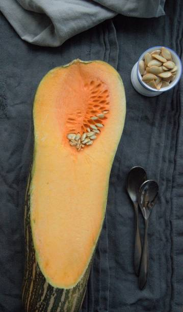Butternut squash sliced in half on a table with seeds in a cup. curcubitaceae orange butternut squash with seeds on a table werken stock pictures, royalty-free photos & images