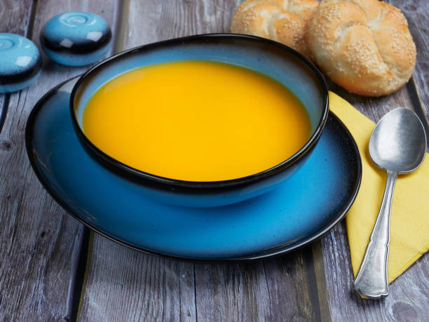 Butternut squash soup in a blue bowl stock photo
