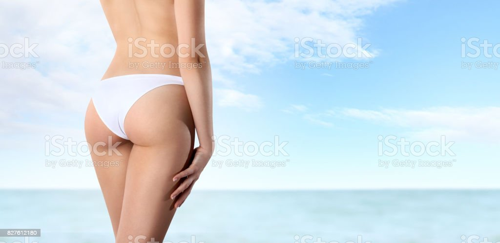 buttocks of woman seen from behind on blue sea and sky background, body care concept stock photo