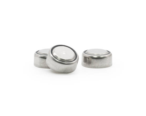 Button cell on isolated background. Small watch lithium battery ( Clipping path or cutout object for montage ) stock photo