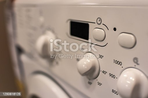 Button of time and operating mode on the washing machine. Selective focus. The concept of home appliances.