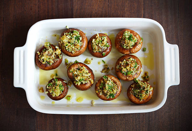 knopfleiste, portobello-pilze gefüllt mit käse und kräutern - gebackene champignons stock-fotos und bilder