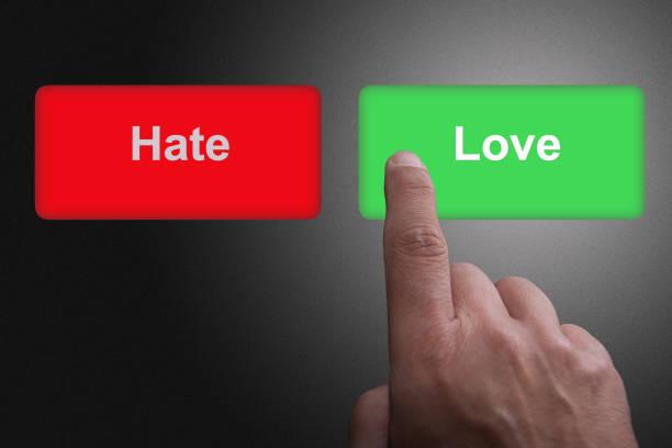 Knöpfe mit geschriebener Liebe und Hass und Zeigefinger, auf grauem Gefälle – Foto