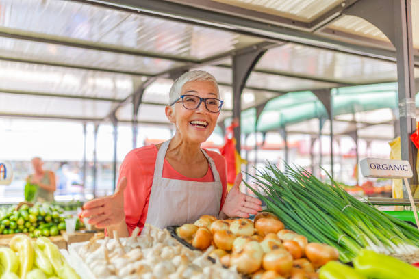 Buy Local at the Farmer's Market. Buy Local at the Farmer's Market. Greengrocer selling organic fresh agricultural product at farmer market. Female Stall Holder At Farmers Fresh Food Market farmer's market stock pictures, royalty-free photos & images
