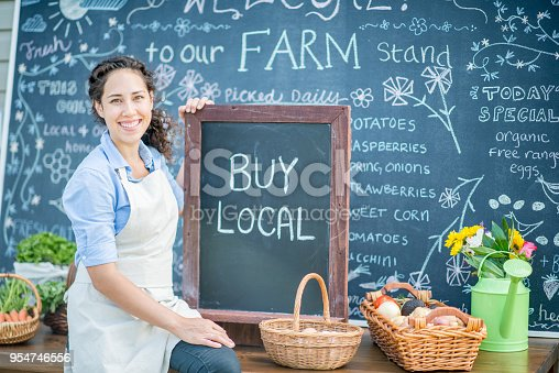 A portrait of a young woman who is wearing an apron and holding a chalkboard that says