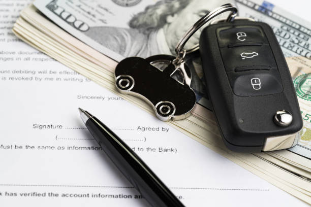 Buy or sell car, purchase or rent automobile service with key with car keychain on pile of US Dollar banknotes money on printed contract paper and pen to sign, finance installment or debt awareness stock photo