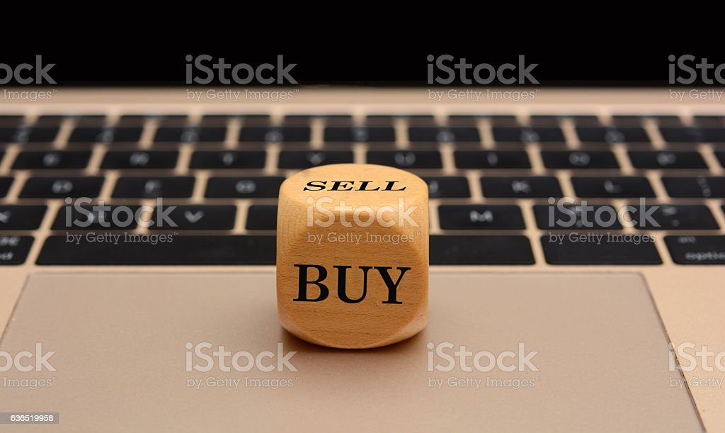 Buy Sell Concept on Wooden Dice Cube laptop in background stock photo