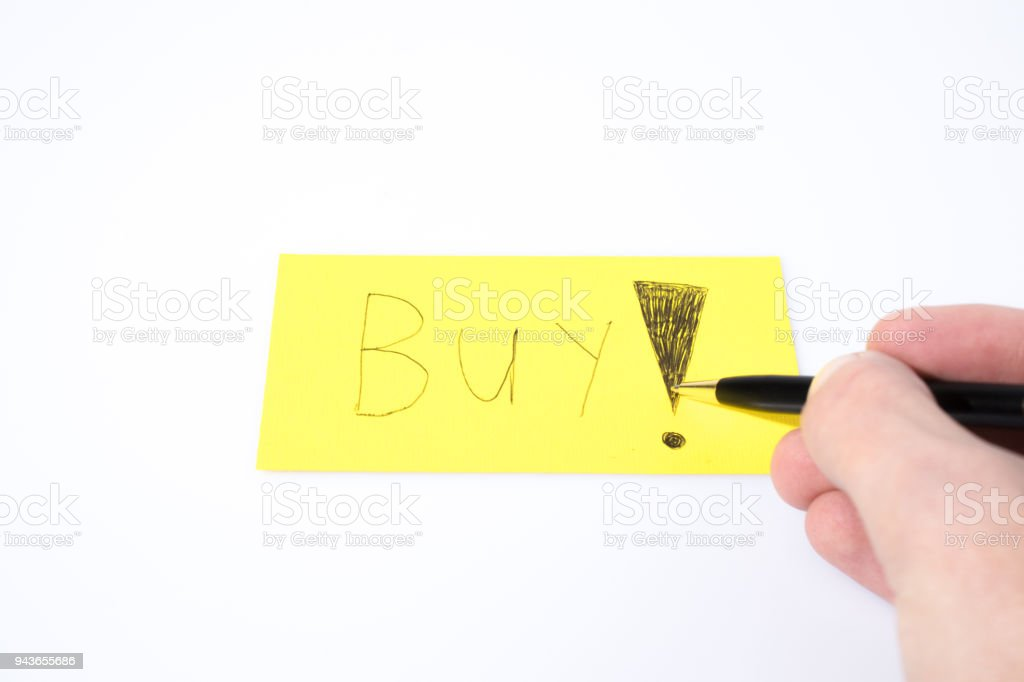 Buy write with a pen and a hand on a yellow paper composition stock photo