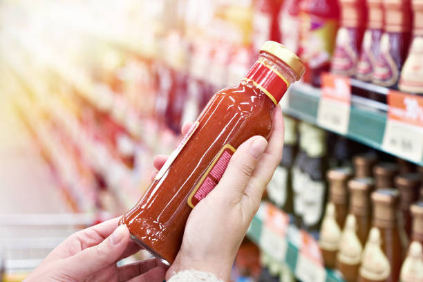 Buyer hands with bottle of chilli sauce in store Buyer hands with bottle of chilli sauce in store savory sauce stock pictures, royalty-free photos & images