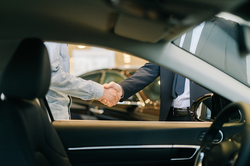Buyer of car shaking hands with seller in auto dealership, view from interior of car. Close-up of handshake of business people. Concept of choosing and buying new car at showroom.