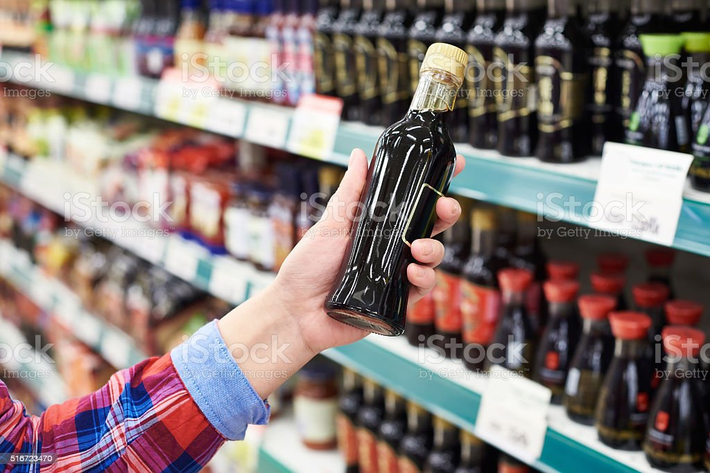 Buyer with soy sauce in store stock photo