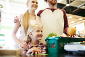 Happy family of three standing by cash-register in modern hypermarket