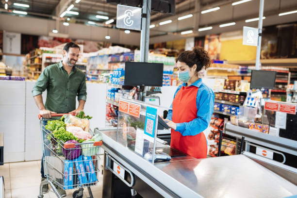 Buyers with protective face mask in supermarket during coronavirus covid-19 pandemic stock photo