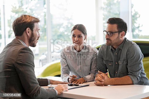 988321834 istock photo Buying a car in auto salon ,young couple with car salesman 1032054036