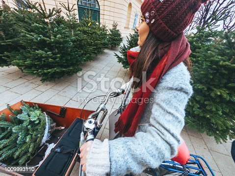 Young woman is buying her Christmas tree and pushing her cargo bike