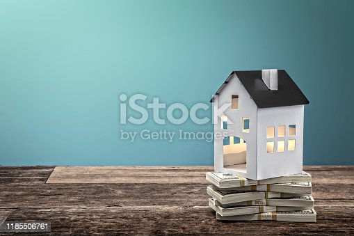 This is a photograph of a small toy country home with a stack of hundred dollar bills symbolize buying any House, investment, mortgage, etc.