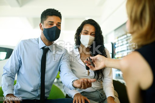 Young mixed race couple buying a new car in a car dealership. Group of multi ethnic people.