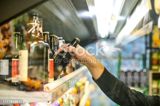 Unrecognizable man buying beer in a supermarket store.