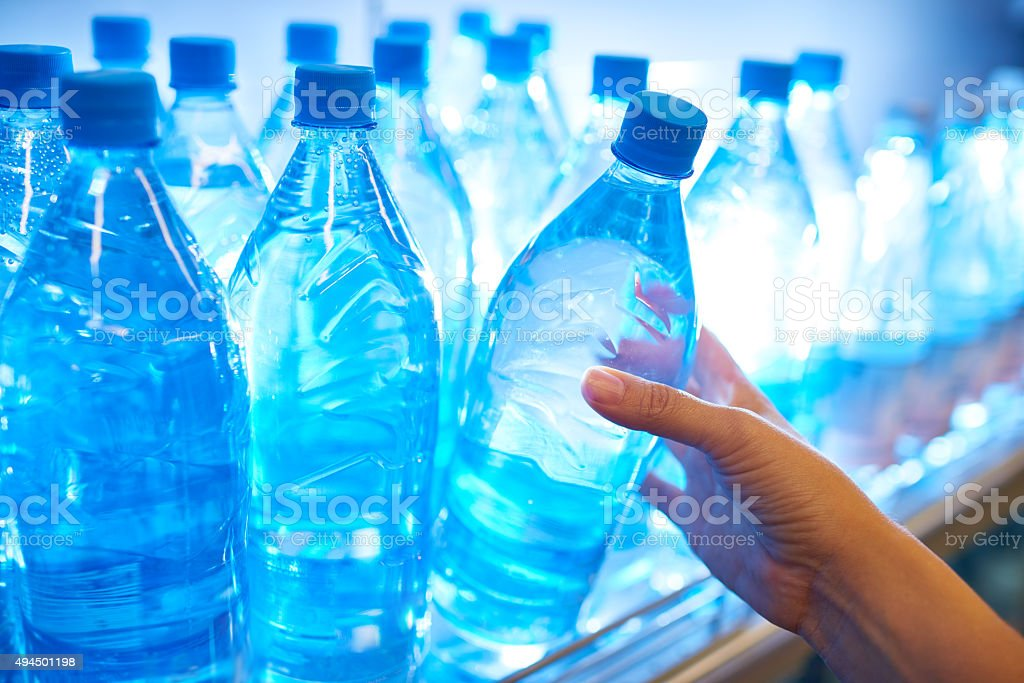 Buying bottle of water Human hand taking mineral water from shelf in supermarket 2015 Stock Photo