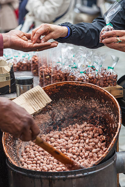 buying candied nuts in montmartre - carolinemaryan stock pictures, royalty-free photos & images