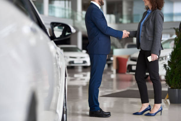 Buying car Businesswoman buying car in automobile dealership and shaking hand of manager as symbol of successful deal car salesperson stock pictures, royalty-free photos & images