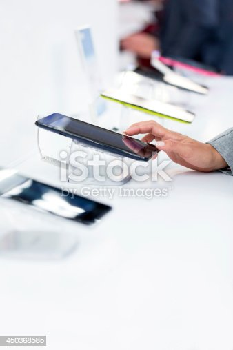 Unrecognizable woman choosing digital tablet in electronics store, copy space